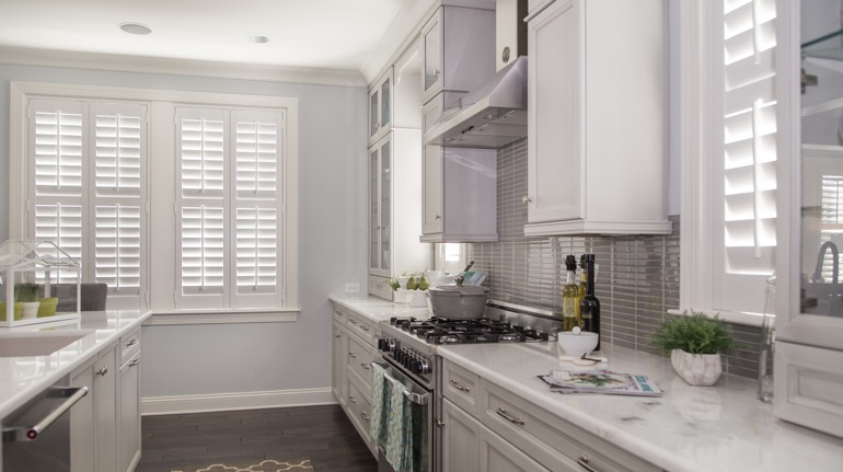 Plantation shutters in Boston kitchen with white cabinets.