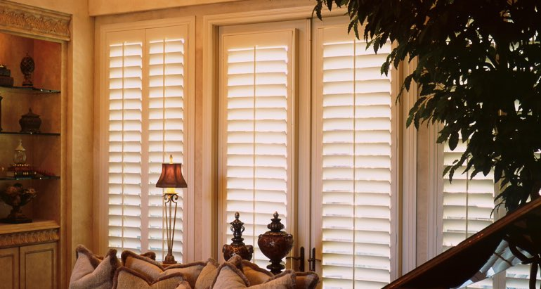 Plantation shutters on french door and window in Boston living room