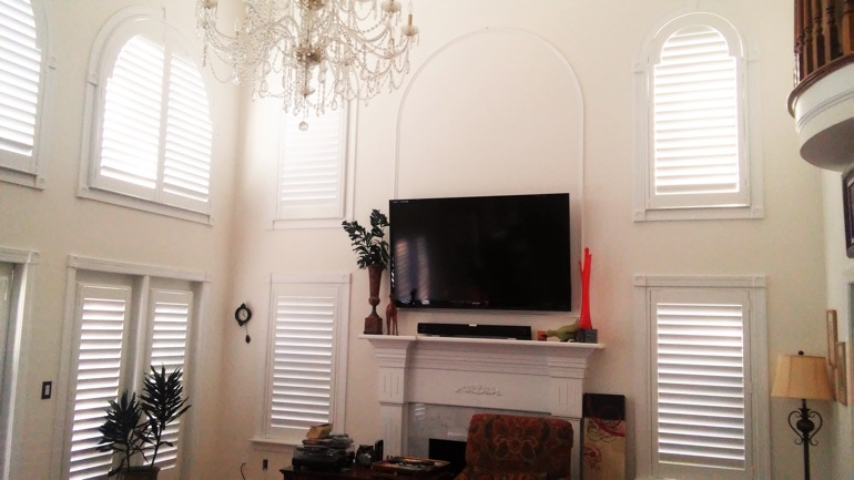 Boston great room with mounted television and arc windows.