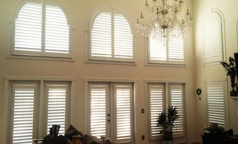 Entertainment room in open concept Boston home with plantation shutters on arch windows.