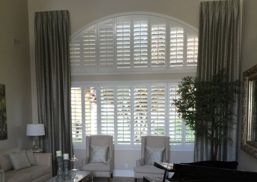 Plantation shutters on a large arched Boston window