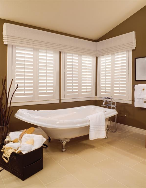 White plantation shutters give a crisp look to a brown bathroom