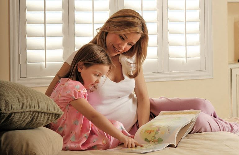Parent and daughter reading on bed with shuttered windows.