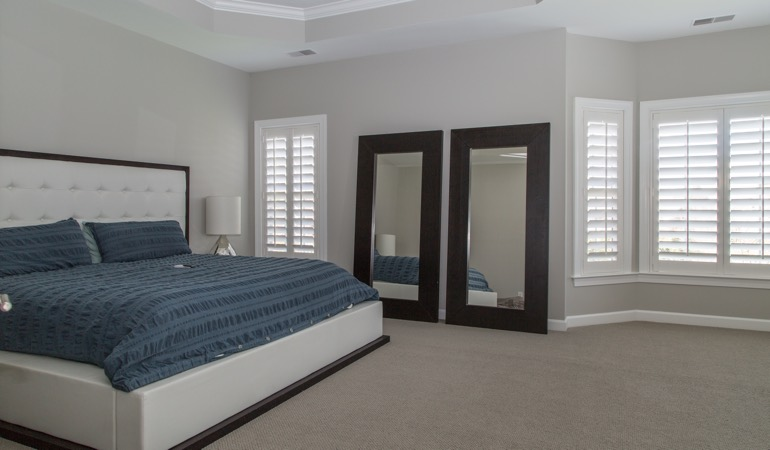 White shutters in a minimalist bedroom in Boston.