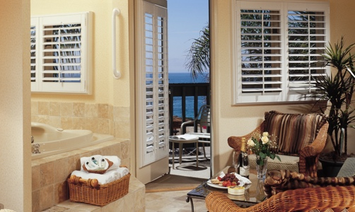 Plantation shutters on casement windows in a lakefront room.
