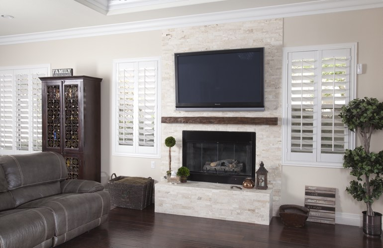 White plantation shutters in a Boston living room with plank hardwood floors.