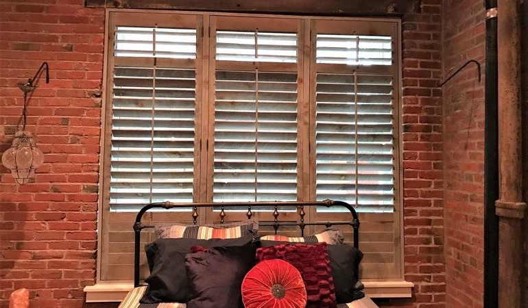 Reclaimed wood shutters surrounded by brick wall.