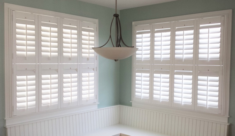 Pastel green wall in Boston kitchen with shutters.