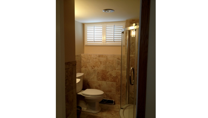 Small basement bathroom window covered in white plantation shutters