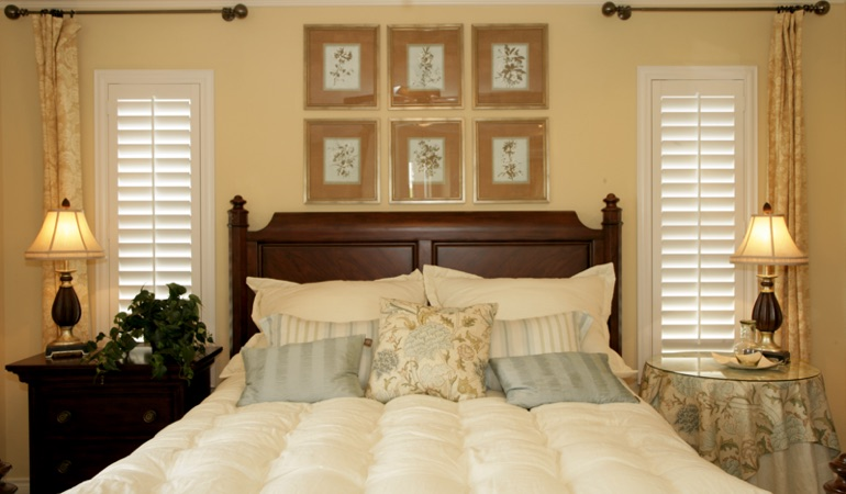 Beige bedroom with white plantation shutters covering windows in Boston