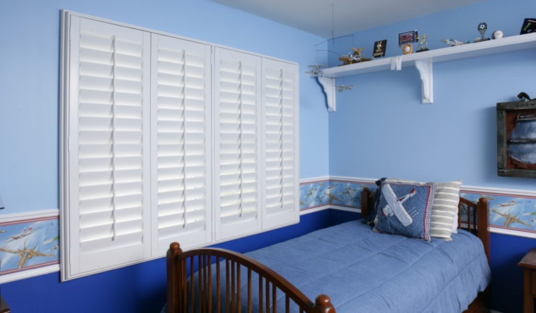 White plantation shutters in blue kids bedroom in Boston